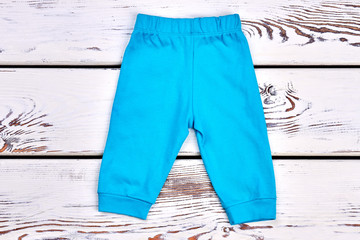 Baby boy blue trousers. Infant boy blue cotton pants on white wooden background. Newborn kids outfit.