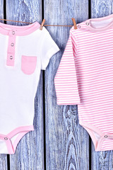 Infants pure clothes hanging on rope. Toddler kids beautiful jumpsuits drying on clothesline on grey wooden background.