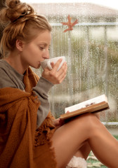 Woman wrapped in a warm plaid blanket drinking hot tea and reading a book in autumn