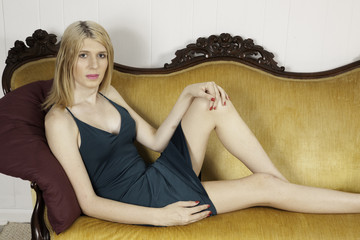 Blond woman laying on a couch looking thoughtful