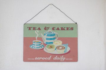 A simple old picture in a vintage style is an invitation to tea and cakes. It hangs on a white wall of a kitchen or cafe.