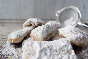 Homemade beignets with powdered sugar in rustic setting detail