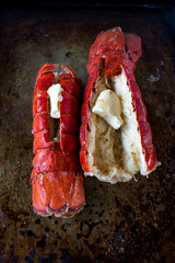 Two cooked red lobster tails with butter