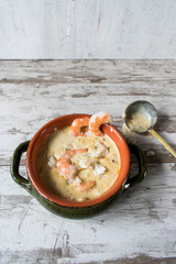 Seafood chowder top view with ladle in white rustic background