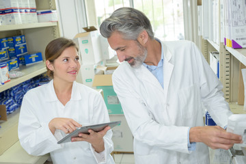 woman pointing at laptop screen when talking to pharmacist