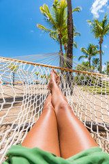 Beach hammock vacation woman feet selfie. Girl relaxing taking pov picture of her legs and feet sun tanning in tropical summer destination. Travel fun getaway.