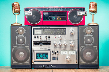 Retro outdated HI FI stereo cassette boom box system, red radio tape recorder from 80s and golden microphones on table front aquamarine background. Vintage old style filtered photo