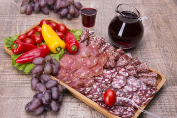 Set of meat delicatessen, tomatoes and peppers, wine on a wooden table.