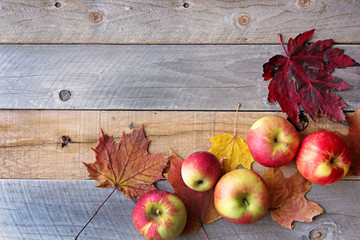 Rustic Fall Decor of Maple Leaves and Apples Frame A Weathered Wood Plank Background