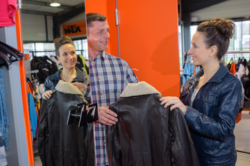 man choosing a leather jacket in a retail store