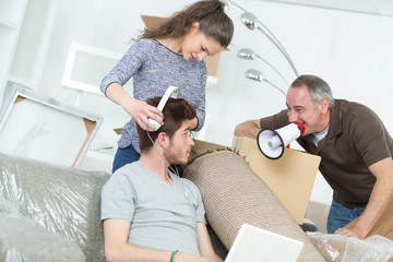 busy woman and dad packing and lazy boyfriend on couch