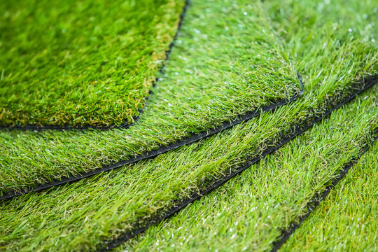 Green artificial turf. Probes examples of artificial turf, floor coverings for playgrounds.