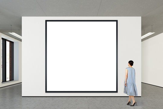 Woman looking at blank poster in modern gallery