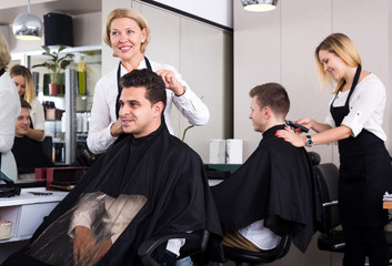 Mature female doing hairstyle for adult man