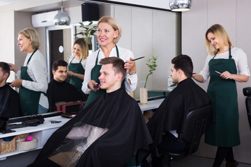 hairdresser cutting hair of male