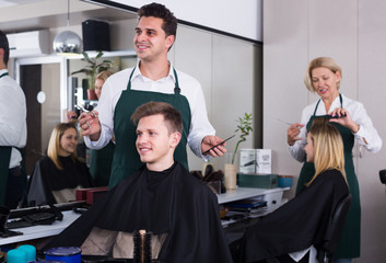 Positive male hairstyler serving teenager in chair