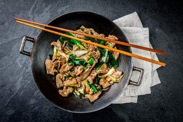 Traditional chinese mongolian beef stir fry in chinese cast iron wok with cooking chopsticks, stone slate background. Top view, copy space