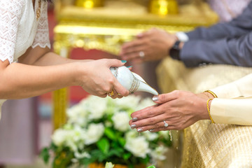 Selective focus with Thai wedding ceremony, water pouring from conch shell to bless the bride.