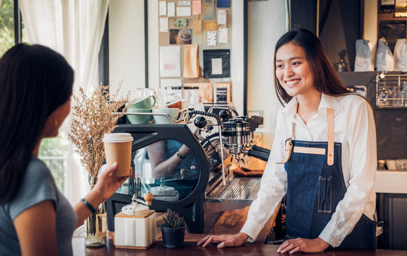 Asian woman barista wear jean apron served to go coffee cup  to customer at bar counter with smile emotion,Cafe restaurant service concept,Owner small business concept