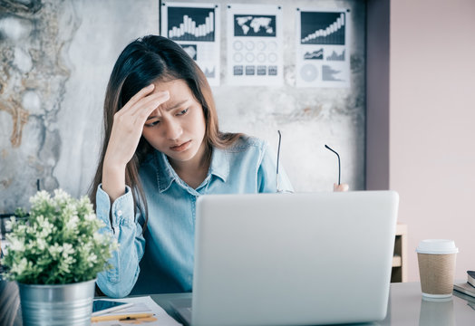 Stressed Asian creative designer woman cover her face with hand and feel upset from work in front of laptop computer on desk at office,Stress office lifestyle concept