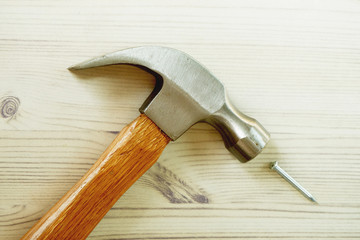 hammer and nail on the white tree floor.