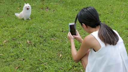 Young Woman taking photo with cellphone on her dog