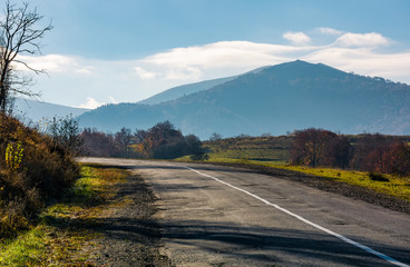 countryside road in autumnal mountainous area. beautiful view of high mountain in the distance in fine forenoon weather