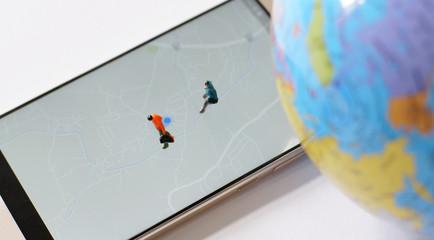 Miniature traveler walking on world map. Travel concept.