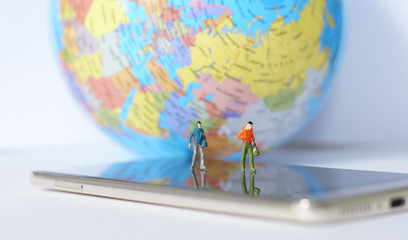 Miniature traveler walking on world map. Travel concept.
