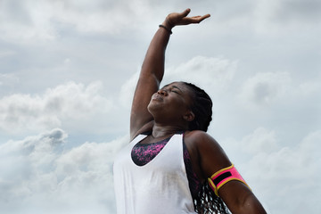 sporty african woman  sweating after exercising under rain  over sky  background.