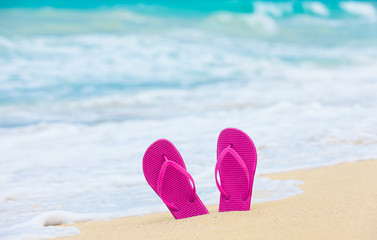 Pair of pink slippers on white sand beach.