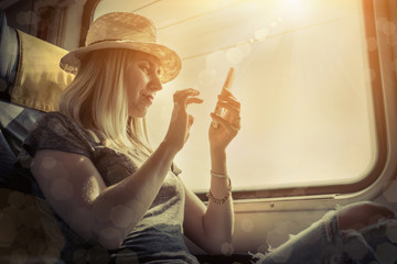Woman sitting at train and looking to mobil phone under sunlight