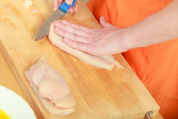 Man cutting raw chicken meat on wooden board