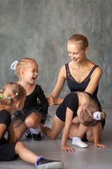 An adult beautiful ballerina in a black dress, white pantyhose and pointe shoes sits on the floor and talks with little girls about ballerinas about dances, girls laugh and have fun