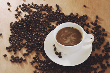 Coffee cup and coffe bean on wood background
