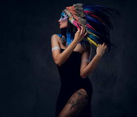 Female with native Indian feather hat and colorful makeup.