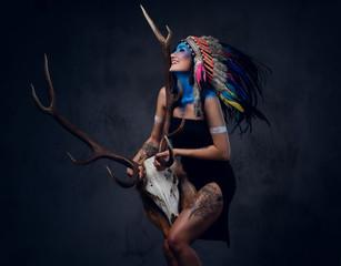 Indian female holds an antler skull.