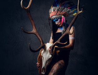 Indian female holds an antler skull.