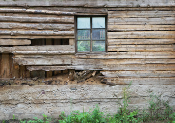 The rotten wooden wall of a village barn with a window
