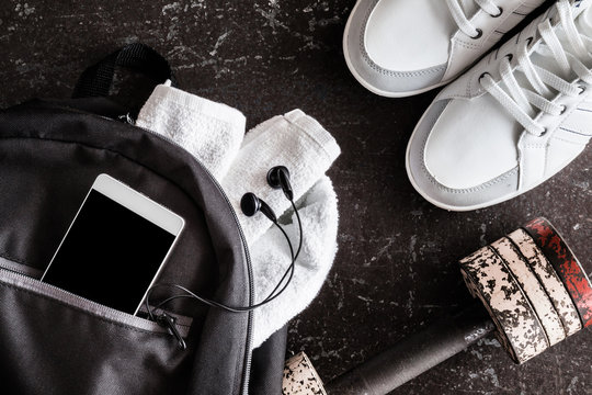 Fitness accessories on the dark floor in the gym. Sneakers, dumbbell, black sport bag, smart phone, towels. Cares about a body. Sport concept. Top view.