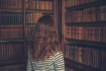 Woman looking at books in an old library
