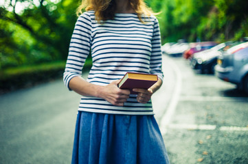 Young woman with book in car park
