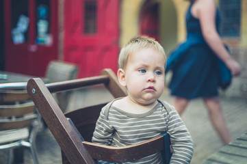 Little baby on high chair at table outside