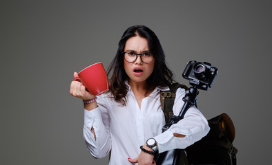Female holds digital photo camera and a red coffee cup over grey background.