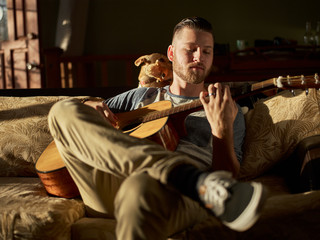 Man Playing Guitar On Sofa With Dog At Home
