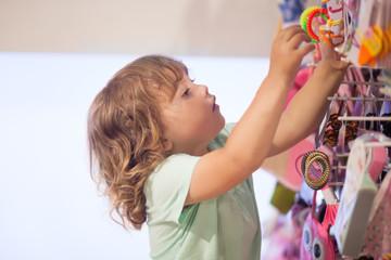 Cute little girl choosing accessories in the shop