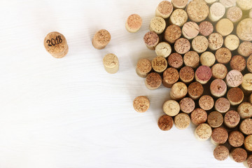 different from others/  large wine cork with the number 2018 next to a lot of older ones on the table top view