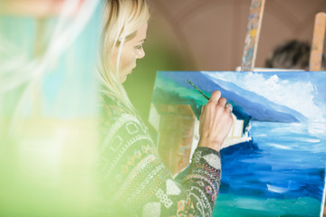 woman artist with a brush in her hand draws on canvas