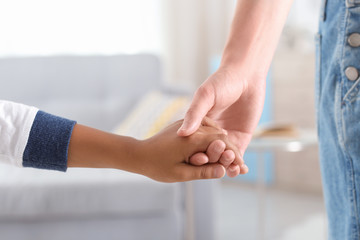 Woman holding hand of small African-American child. Adoption concept