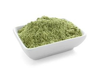 Bowl of barley powder on white background